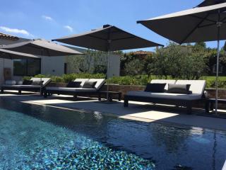 Agencement de bord de piscine avec parasols et bains de soleil